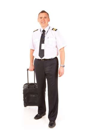 epaulettes: Cheerful pilot wearing uniform with epaulettes standing with trolley bag isolated on white background. Flying for an commercial airline, pilots are usually referred to as airline pilots, with the pilot in command often referred to as the captain.  Stock Photo