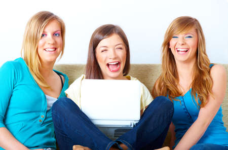 Three happy friends beautiful girls sitting on sofa in home with laptop computer Stock Photo - 8887501