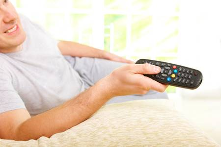 Relaxed man smiling lying on sofa with remote control handheld, watching television in home Stock Photo - 8887262