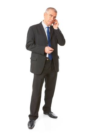 body image: Full body image of mature standing business man wearing dark suit and talking on the mobile phone, isolated over white background