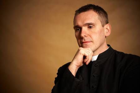 vicar: Thinking priest with hand under chin Stock Photo