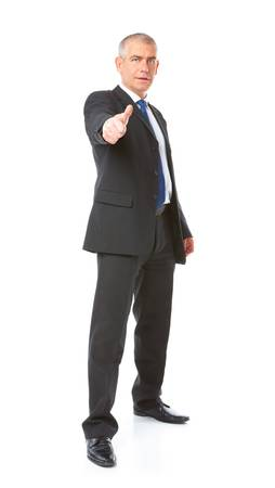 body image: Full body image of mature standing business man wearing dark suit, gesturing thumb up, isolated over white background