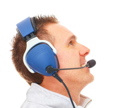 aside: Cheerful man pilot with headset used in aircraft looking upwards aside isolated on white background. Similar headphones are also used in communication so image also suits for radio TV  sport commentator and ATC controller. Stock Photo