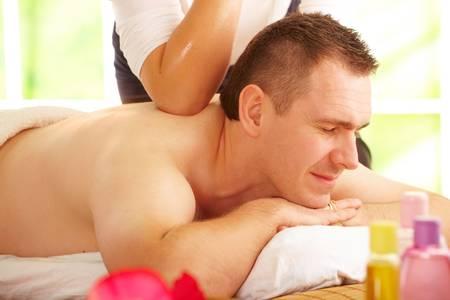 Male enjoying kind of Thai massage treatment with female hand back photo