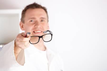 hyperopia: Oculista ottico maschile che offre occhiali a un paziente