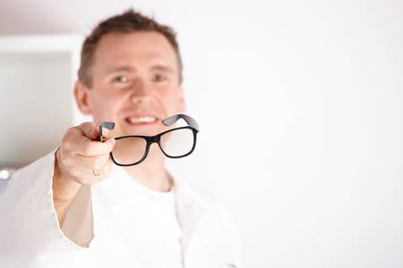 diopter: Oculista �ptico masculino ofreciendo gafas a un paciente