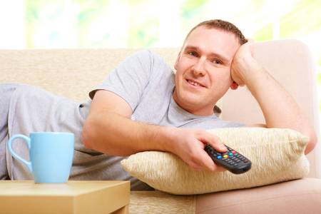 Relaxed handsome man smiling lying on sofa with remote control handheld, watching television in home Stock Photo - 8887422