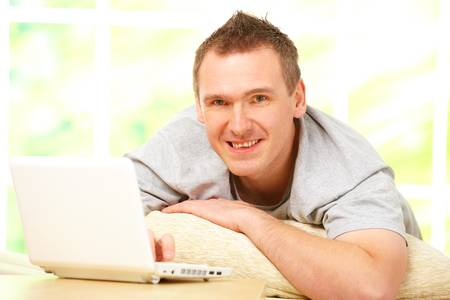 Portrait of a man relaxing on sofa in home with laptop and smiling. Stock Photo - 8887360