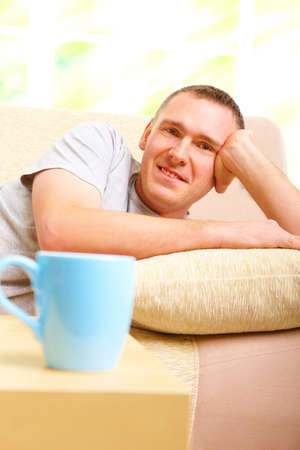 Portrait of a man relaxing on sofa in home and smiling. Blue cup in foreground. Stock Photo - 8887385