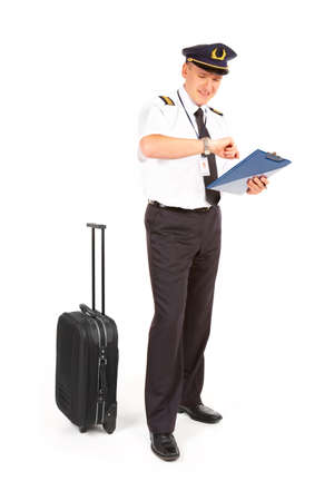 epaulettes: Cheerful pilot wearing uniform with epaulettes standing with trolley bag and documents, checking time isolated on white background.  Stock Photo
