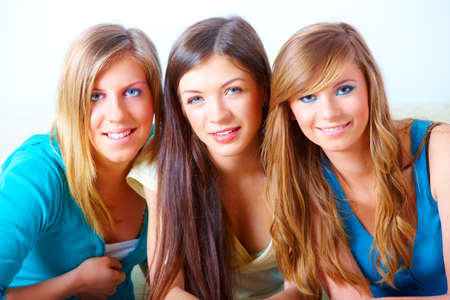 Two beautiful girls sitting on sofa in home with faces close to each other Stock Photo - 8887529