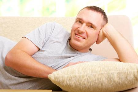 Portrait of a man relaxing on sofa in home and smiling. Stock Photo - 8887471