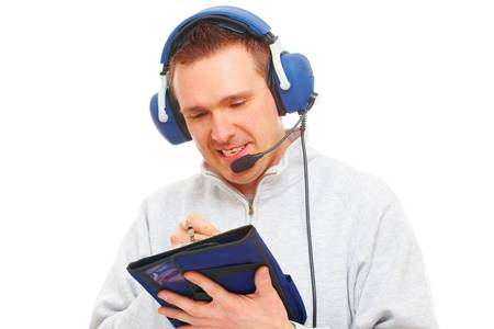 commentator: Cheerful man pilot with headset used in aircraft taking notes on knee-pad, isolated on white background. Similar headphones are also used in communication so image also suits for radio TV  sport commentator and ATC controller. Stock Photo