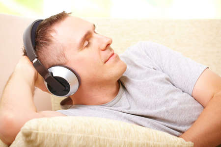 Face of relaxed man listening music with headphones with closed eyes laying on sofa at home and gently smiling. Stock Photo - 8887421