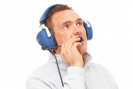 commentator: Cheerful man pilot with headset used in aircraft looking upwards aside isolated on white background. Similar headphones are also used in communication so image also suits for radio TV  sport commentator and ATC controller. Stock Photo