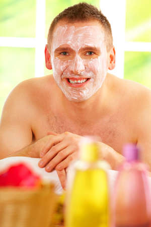 Happy man resting in sunny spa salon laying with facial mask  with cosmetics in foreground. Stock Photo - 8887341