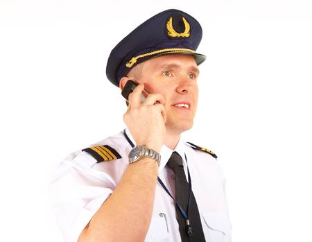 aircrew: Cheerful pilot wearing uniform with epaulettes and hat with golden wings, talking on mobile phone, standing isolated on white background.