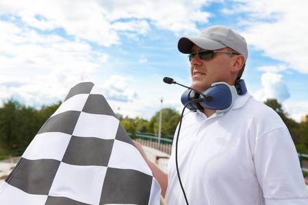 Flagman with checkered flag meaning that winner has just crossed the finish line. Stock Photo - 8887460