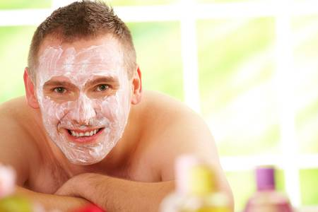 destress: Happy man resting in sunny spa salon laying with facial mask  with cosmetics in foreground.