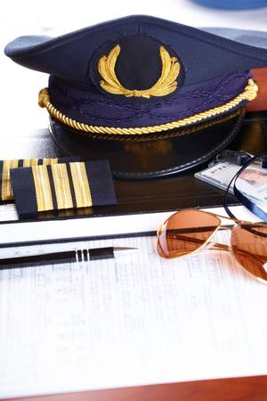 airline uniform: Professional airline pilot hat and id holder with epaulets and sun glasses laying on log book and flight plan.