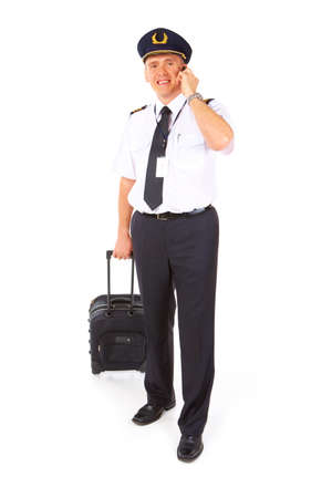 epaulettes: Cheerful commercial pilot wearing uniform with epaulettes and hat standing with trolley bag isolated on white background.