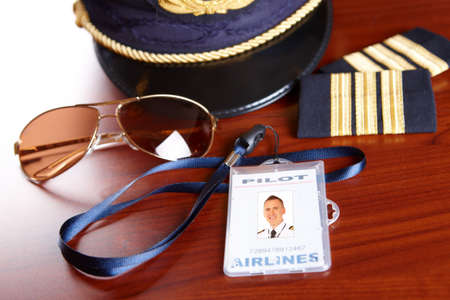 airline uniform: Professional airline pilot hat and id holder with epaulets and sun glasses laying on table