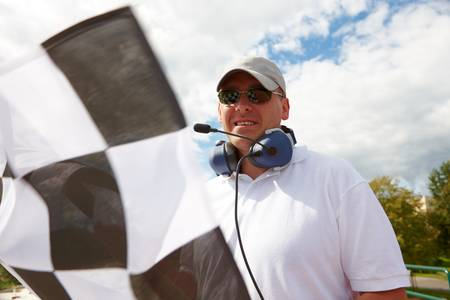 Flagman with checkered flag meaning that winner has just crossed the finish line. Stock Photo - 8887405