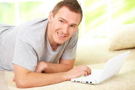 Portrait of a man relaxing on sofa in home with laptop and smiling. photo