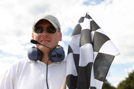 Flagman with checkered flag meaning that winner has just crossed the finish line. Stock Photo - 8887381