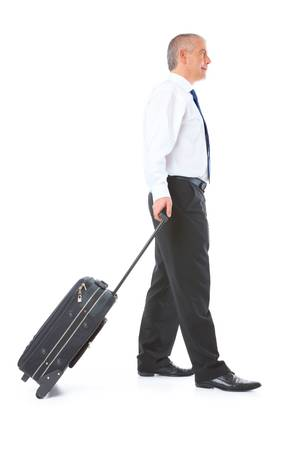 body image: Full body image of mature business man walking with luggage trolley, isolated over white background Stock Photo