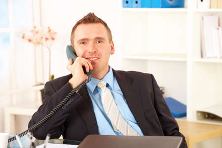 talking telephone: Happy businessman sitting at desk in office, talking on landline phone with laptop and smiling. Documents in background.