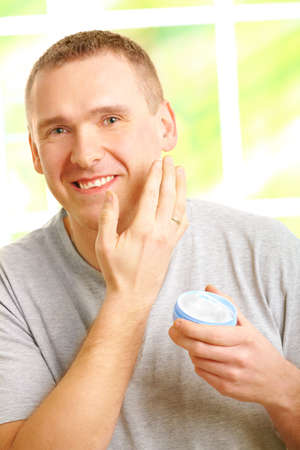 Happy man wearing casual clothes applying facial cream on skin. Stock Photo - 8887445