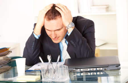 Stressed businessman sitting at desk holding his head and worrying Stock Photo - 8887409