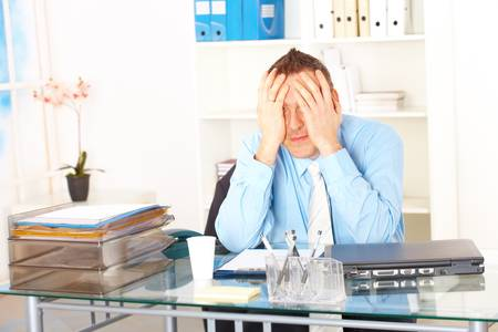 Stressed businessman sitting at desk holding his head and worrying Stock Photo - 8887278