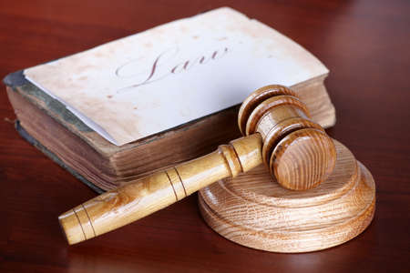Judges wooden gavel with very old book and paper with word law in the background. photo
