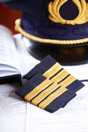 flight crew: Professional airline pilot hat and  epaulets  laying on log book and flight plan.
