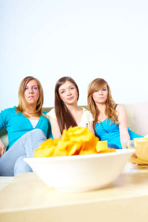 Three happy friends beautiful girls sitting on sofa in home with chips photo