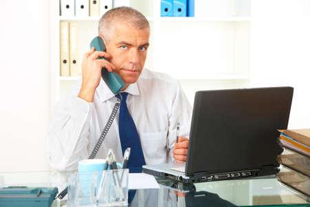 talking businessman: Maduro empresario sentado en el escritorio en la Oficina con tel�fono de l�nea fija y port�til, documentos en segundo plano.