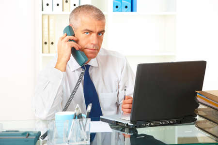 Mature businessman sitting at desk in office with landline phone and laptop, documents in background. Stock Photo - 8887339