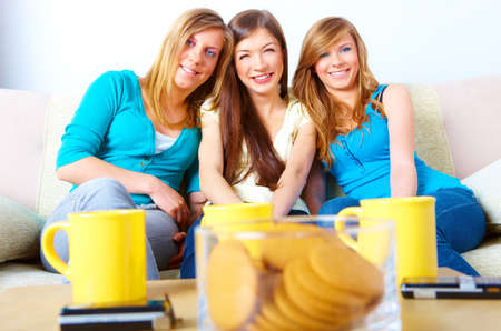 Three happy friends beautiful girls sitting on sofa in home with cups, cookies and phones in the foreground.  photo