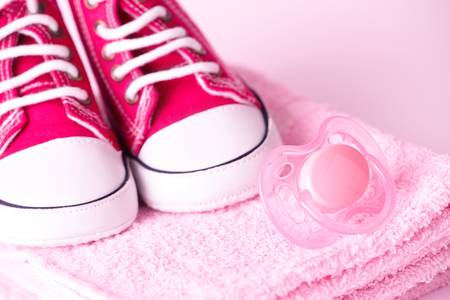 Pink dummy and cute baby shoes on towel Stock Photo - 8887345