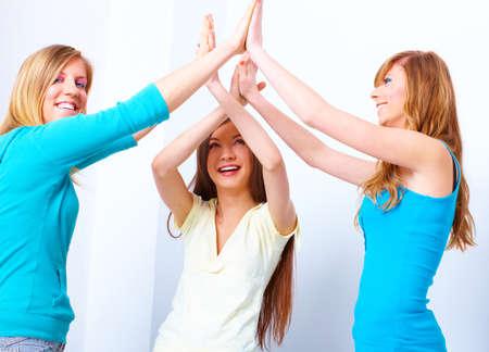 Three happy friends, beautiful girls giving a five photo