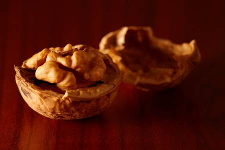 nutshell: Walnut and nutshell on wooden table. Nice side lighting. Stock Photo