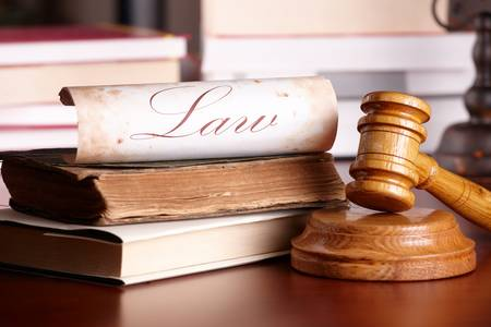 barrister: Judges wooden gavel with very old books and paper with word law in the background.