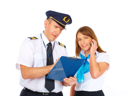 airline uniform: Flight crew wearing uniforms. Cheerful pilot taking notes and flight attendant with mobile phone, isolated over white background