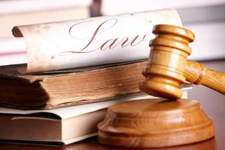 criminal law: Judges wooden gavel with very old books and paper with word law