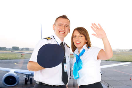aircrew: Flight crew. Cheerful pilot with hat in hand and flight attendant waving wearing uniforms with airliner standing at the airport.