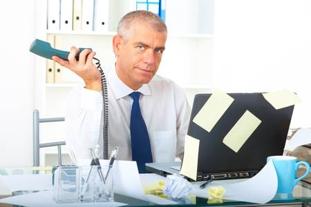 Stressed overworked mature businessman sitting at desk with phone and laptop with many post it stickers Stock Photo - 8887370