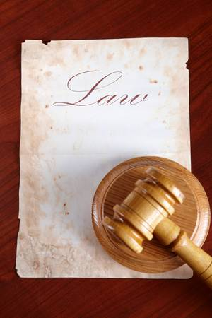 legislation: Old paper with word law and judges wooden gavel
