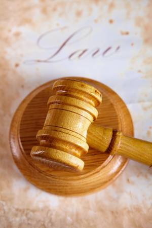 Judges wooden gavel with very old paper with word law in the background. Stock Photo - 8887389